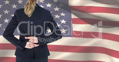 Midsection of female professional crossing fingers against American flag