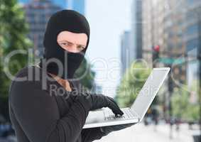 Criminal Man in balaclava on laptop in front of city