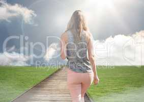 Woman walking up path to blue sky sun