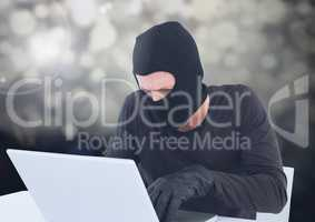 Criminal in balaclava with laptop in sparkling lights