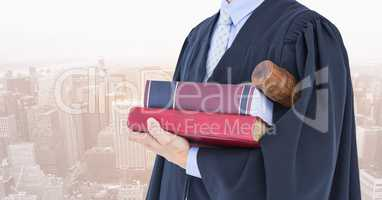 Midsection of judge with books and gavel against city