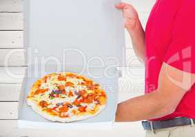 Foreground of the pizza in the box with the deliveryman. wood background