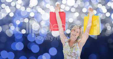 Happy woman with arms raised holding shopping bags