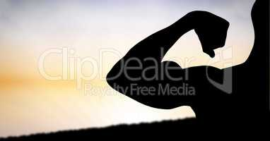 Silhouette muscular man flexing muscles against sky