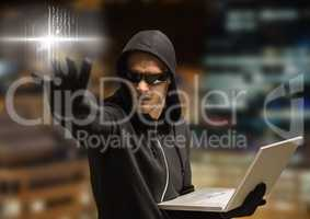 Criminal in hood on laptop in front of night city