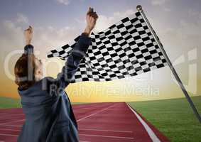 Business woman cheering on track against checkered flag and evening sky