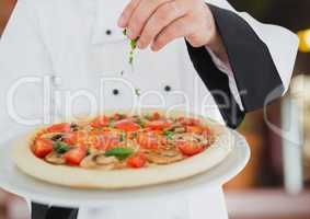 Chef with the pizza in foregroun,  in the restaurant. pizza delivery