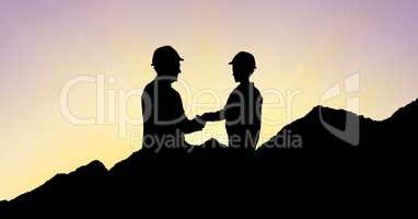 Silhouette architects shaking hands on mountains during sunset