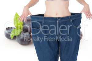 Midsection of woman in loose jeans by blueberries representing weight loss concept
