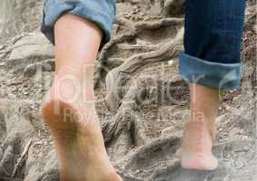 Bare feet walking climbing rough tree roots terrain hill