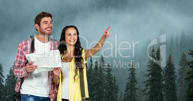 Woman pointing while man holding map during traveling on mountain in foggy weather