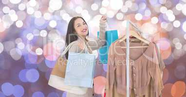 Happy woman shopping by clothes rack over blurred background