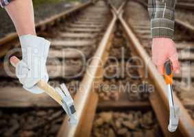 hands with hammers in the railroad tracks