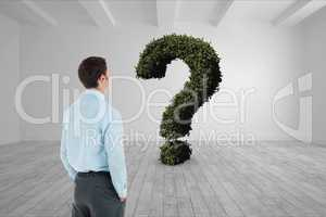 Businessman looking at question mark made of plants