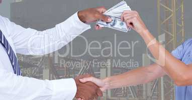 Business people shaking hands while passing money representing corruption concept