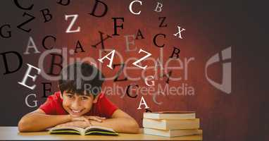 Happy boy with book leaning on table against flying letters