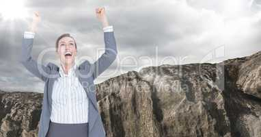 Business woman cheering with flare against rock and cloudy sky
