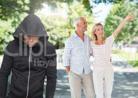 Criminal in hood in front of couple walking in park