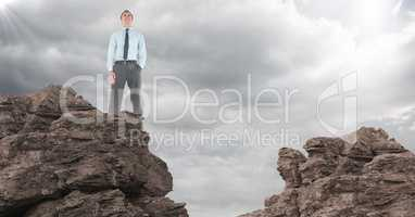Business man hand in pocket on rocks against clouds with flare