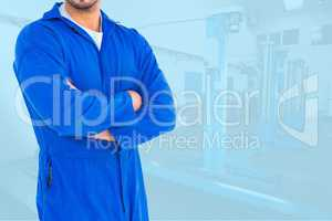 Midsection of worker with arms crossed standing in workshop