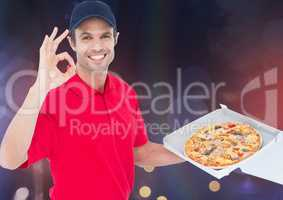 Happy delivery man sawing the pizza. Lights background