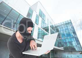 Criminal Man in balaclava on laptop in front of glass building