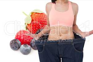 Midsection of woman in loose jeans by fruits representing weight loss concept