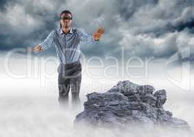 Business man blindfolded on misty mountain peak against storm clouds