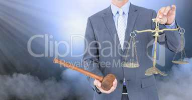 Judge with balance scale and hammer in front of clouds