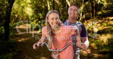 Happy couple riding cycle in forest