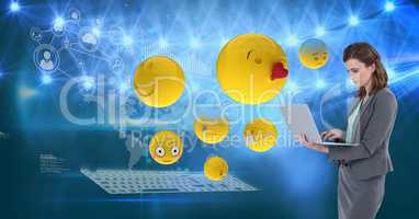 Digital composite image of emojis flying by businesswoman using laptop against tech graphics in back