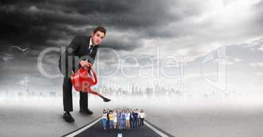 Large businessman pouring water on employees against storm clouds