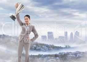 Business woman with trophy on misty mountain peak against skyline