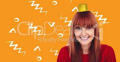 Woman in party hat against orange background with white patterns