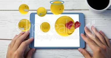 Digitally generated image of emojis flying over hand using tablet computer by drink on table