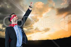 Businessman in super hero costume with hand raised against sky