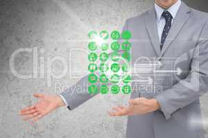 Digital composite image of various icons with businessman gesturing in background