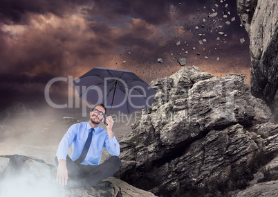 Business man legs crossed with umbrella and mist against falling rocks