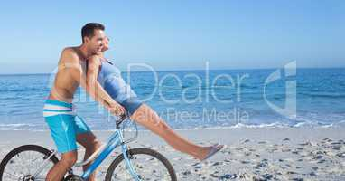 Carefree couple riding cycle at beach