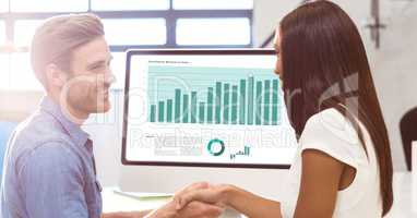 Businessman shaking hand with colleague for success of presentation on monitor