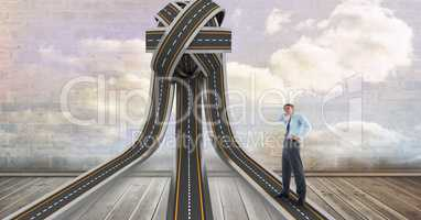 Confused businessman standing on tangled highway