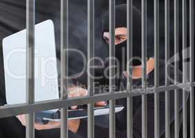 Criminal in balaclava with laptop behind prison bars