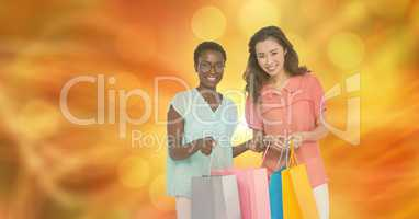 Smiling women with shopping bags over blur background