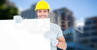 Happy worker wearing hardhat while holding blank bill board
