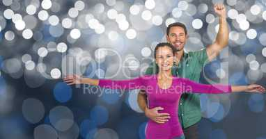 Smiling man and woman with arms raised over bokeh