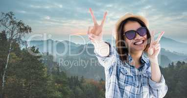 Happy woman showing victory sign while traveling on mountains