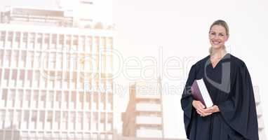 Portrait of smiling judge holding book in city