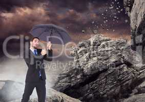 Business man standing with umbrella and mist against falling rocks