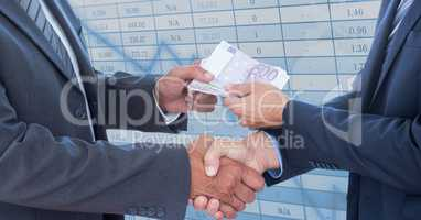 Midsection of business people shaking hands while holding money representing corruption concept