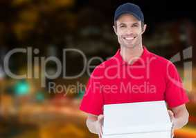Happy deliveryman with the boxes of the pizza in the city at night. Lights